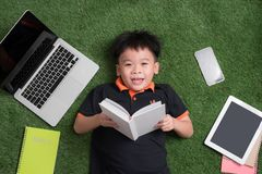 Seven years old child reading a book lying on the grass stock photos