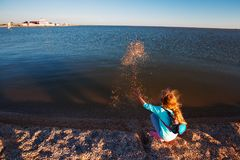 Seven years old girl on the beach at sunset time.  royalty free stock photos