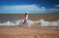 Seven years old girl in summer dress running along the sea at sunny day.  stock photography
