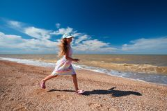 Seven years old girl in summer dress running along the sea at sunny day.  stock photos