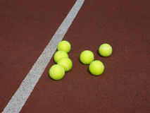 Seven Yellow tennis balls on brown court Royalty Free Stock Photos