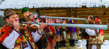 Seventh Ethnic Festival Christmas Carols in the old village. Uzhgorod, Ukraine - January 15, 2017: Member of folklore band plays on trembita during the seventh stock photography
