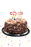 Seventy fifth birthday or anniversary. Chocolate birthday cake surrounded by confetti with lit candle for a seventy fifth birthday or anniversary celebration Stock Photo
