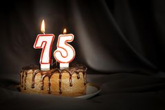 Seventy five years anniversary. Birthday chocolate cake with white burning candles in the form of number Seventy five. Dark background with black cloth stock photo