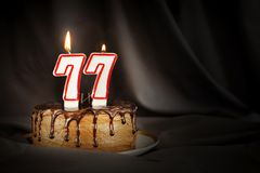 Seventy seven years anniversary. Birthday chocolate cake with white burning candles in the form of number Seventy seven. Dark background with black cloth stock photos