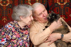 Seventy year old couple with cat. On sofa at home Royalty Free Stock Photos