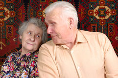 Seventy year old couple smiling at home. Seventy year old couple looking each other and smiling at home Royalty Free Stock Image