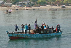 Several African men floating in boat along the shore. Royalty Free Stock Images