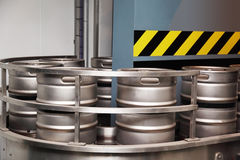 Several aluminum beer barrels move on conveyor Stock Images
