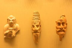 Several ancient head casts are suspended on the surface of a pink shade. The figures are part of the culture of a certain people royalty free stock photography