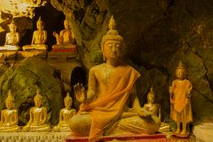 Several ancient sculptures of a Buddha, temple of Wat Tham Khao Luang. Phetchaburi, Thailand. Several ancient sculptures of a seated Buddha in the interior of royalty free stock photo