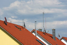 Several antennas on the roofs. Several antennas and chimneys on the top of the roofs stock images