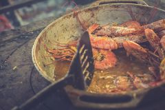 Several appetizing large shrimps in sauce with lemon lie in a frying pan. Toned image.  stock photo