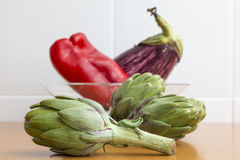Several artichokes on the table, an eggplant and pepper in a bow Stock Image