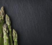 Several asparagus framing stone copyspace. Stock Photos