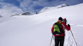 Several backcountry skiers hike and climb to a remote mountain peak in Switzerland on a beautiful winter day. Several backcountry skiers climb and hike over a stock photo