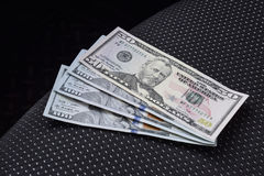Several banknotes American dollars lie on the car seat. The money in the car.  Stock Image