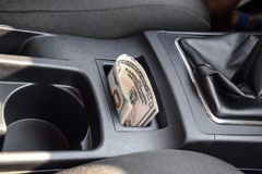 Several banknotes American dollars lie in the niche of the central console of the car. The money in the car Stock Photography