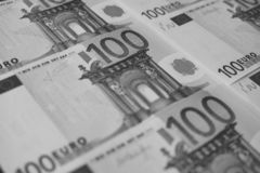 Several banknotes of 100 euros close-up, monochrome royalty free stock image