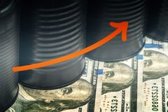Several barrels of oil on dollars and a red arrow up - concept of higher oil prices.  stock photography
