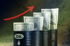 Several barrels of oil with dollars and a red arrow up - concept of higher oil prices.  royalty free stock images