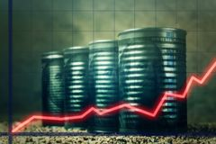Several barrels of oil with dollars and a red graph up - concept of higher oil prices.  royalty free stock images