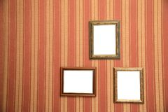 Several beautiful frames for photos of gold on a striped red wall stock photos