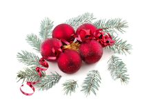 Several red Christmas balls are decorated with a red serpentine and sprigs of spruce. Isolated on white. Royalty Free Stock Photos