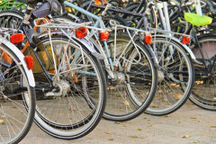 Several bikes in the parking lot. Stock Images