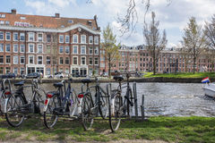 Several bikes on the parking near the grand canal in Amsterdam with brown buildings as background Stock Photos