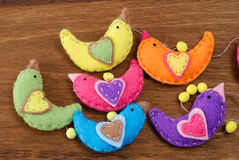 Several birds made of felt on a wooden background Stock Photos