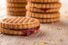 Several biscuits with red homemade marmalade on light board royalty free stock photos