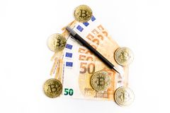 Several bitcoin gold coins next to some euro bills and a pen. On a white background stock images