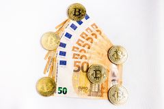 Several bitcoin gold coins next to some euro bills. On a white background stock photos