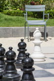 Several black chessmen and white bishop on the street chessboard with chair Royalty Free Stock Images