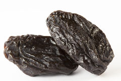 Several black prunes. Few black prunes isolated on white backgroubd royalty free stock image