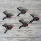 Several black and red spring clamps on the wooden boards. Close up shot of five black and red spring clamps on the grey and white wooden boards, top view with stock images