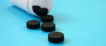 Several black tablets fall out of the plastic jar on the blue surface. Background image on medical and pharmaceutical topics. Activated Charcoal royalty free stock images