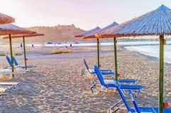 Several blue sunbed, straw umbrella on beautiful beach backgroun Stock Image