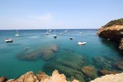 Several boats sail through crystal waters close to beautiful village and beach of Sa Riera Royalty Free Stock Image