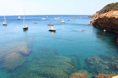 Several boats sail through crystal waters close to beautiful village and beach of Sa Riera Royalty Free Stock Photography