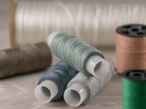 Several bobbins of spools of thread are on a gray background royalty free stock images
