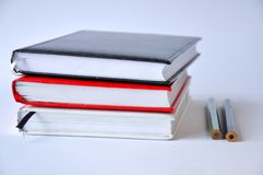 Several books or notebooks on a table on a white background royalty free stock photography