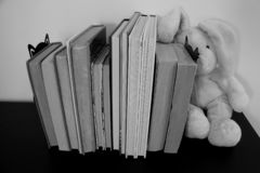 A row of books with a rabbit plush toy on the side. Black and white photo. royalty free stock photo