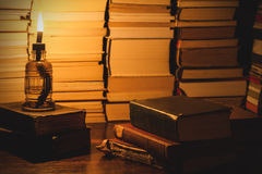Several books, on a table with a lighted torch. Stock Image