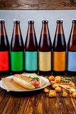 Several bottles of craft beer and snacks on a wooden table. royalty free stock image