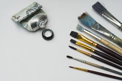 Several brushes of different sizes are on white paper. next to them is a used tube of white paint. royalty free stock photo