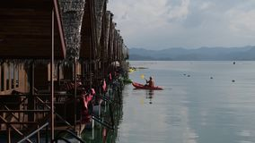 Several bungalows standing on a lake with thatched roofs. People are swimming in a canoe. Kayaks are parked to the pier. Lake Cheow Lan. Khao Sok Thailand stock footage