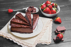 Several cakes cheesecake. Fresh strawberries, chocolate spread, on a white porcelain plate refined, white lace doily on a black wooden background in rustic Stock Images