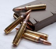 .223 rounds and a loaded magazine. Several .223 caliber rounds and a loaded magazine on a white backgroundn Stock Image